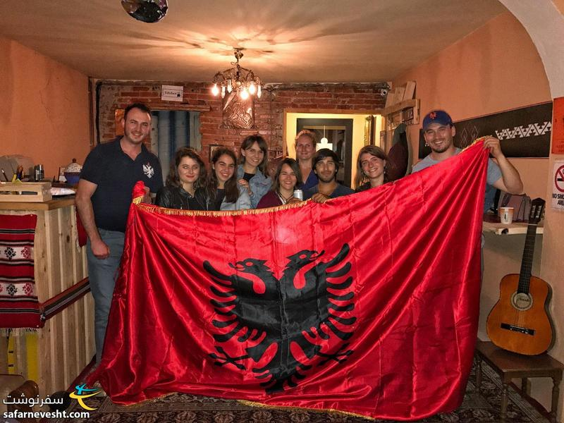 A photo with guests and Albania's flag in ODA hostel